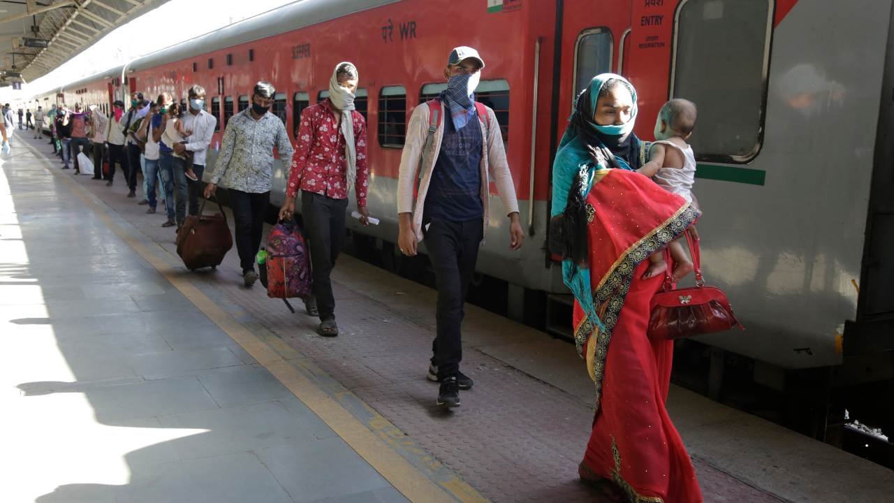 """Indian migrated workers walks towards a coach of a special train to Agra in Uttar Pradesh state, for migrated workers stranded in Gujarat, during a nationwide lockdown to curb the spread of new coronavirus, in Ahmedabad, India, Saturday, May 2, 2020. India has decided to extend the lockdown of its 1.3 billion people for two more weeks, with some relaxations. The government has identified """"red"""" and """"orange"""" zones where coronavirus cases have been found, where stricter measures will continue. In low-risk """"green"""" zones, some movement of people and most economic activities will be allowed. (AP Photo/Ajit Solanki)"""