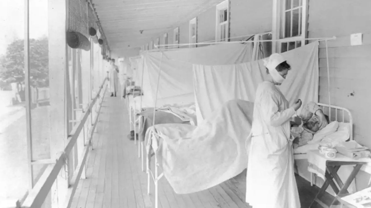 In this November 1918 photo made available by the Library of Congress, a nurse takes the pulse of a patient in the influenza ward of the Walter Reed hospital in Washington.  Image credit: Harris & Ewing/Library of Congress via AP, File