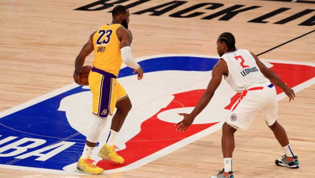 LeBron James of the Los Angeles Lakers dribbles the ball against Kawhi Leonard of the LA Clippers. AP Photo